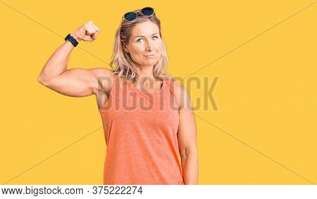 Middle age fit blonde woman wearing casual summer clothes and sunglasses strong person showing arm muscle, confident and proud of power