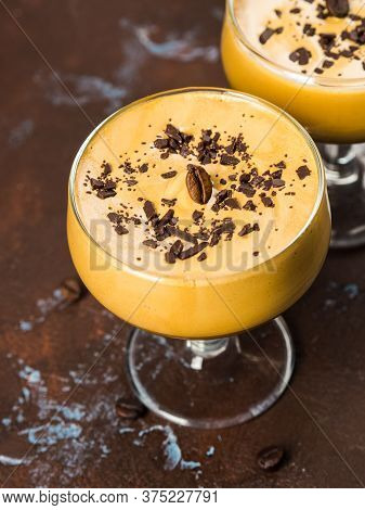Frappe Frothed Cold Coffee Drink In Dessert Glasses On Brown Backdrop