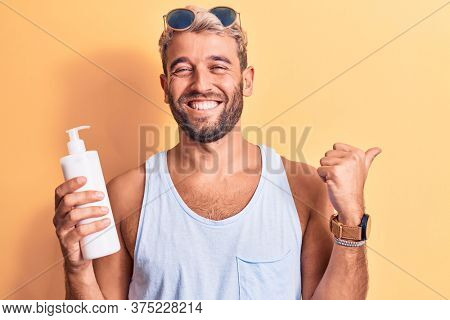 Young handsome blond man with beard on vacation holding bottle of sunscreen to protect skin pointing thumb up to the side smiling happy with open mouth