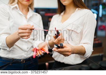 Cosmetician advises woman in cosmetics store
