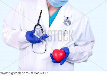 Doctor Cardiologist Holds A Heart And A Syringe In His Hands. Medical Concept.