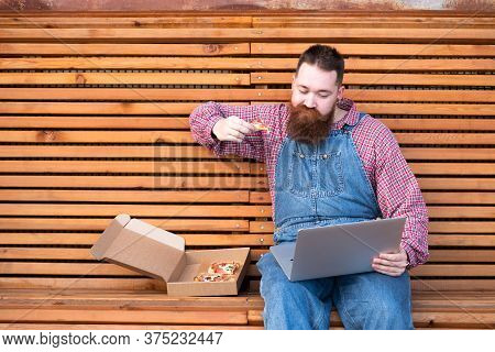 Busy Multitask Bearded Hipster Man In Blue Jeans Overalls, Checked Shirt Working On Laptop And Eatin