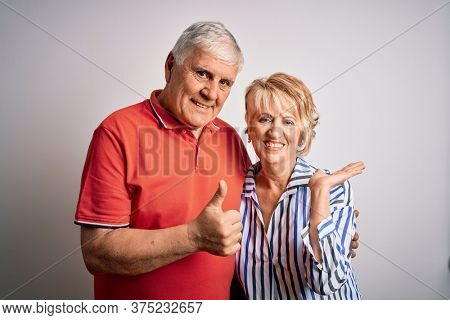 Senior beautiful couple standing together over isolated white background Showing palm hand and doing ok gesture with thumbs up, smiling happy and cheerful
