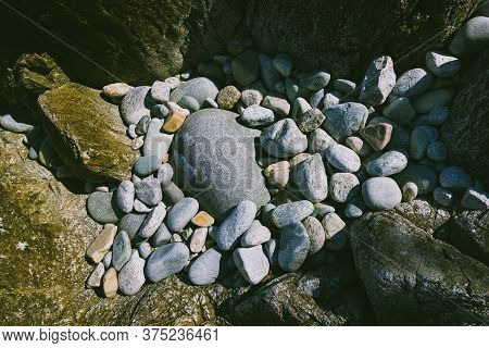 Sea Stone, A Texture Of Mixed Size Pebbles Near The Sea In Summer, A Large Stone Lies Surrounded By
