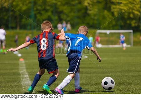 Two Youth Football Players Running In Duel After Ball. Kids Kicking Soccer Match On The Grass Field.