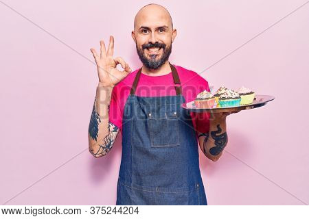 Young handsome man wearing apron holding cupcake doing ok sign with fingers, smiling friendly gesturing excellent symbol