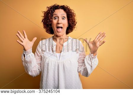 Middle age beautiful curly hair woman wearing casual summer dress over yellow background celebrating crazy and amazed for success with arms raised and open eyes screaming excited. Winner concept