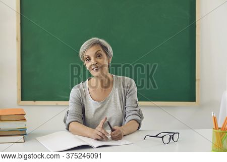 The Teacher Is Looking At The Camera Online. Female Senior Teacher Teaches Students Remotely Using C