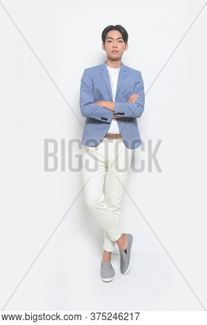 Full body young handsome man wearing in blue suit with T-shirt and white jeans pants and gray  casual shoes, with arms crossed