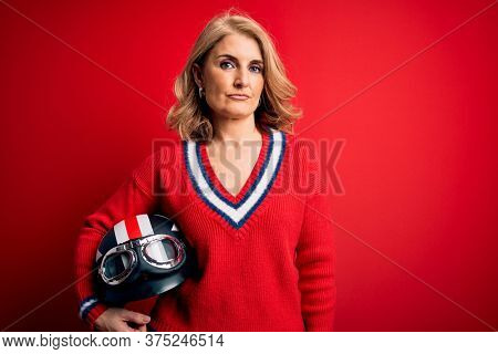 Middle age beautiful blonde motorcyclist woman holding moto helmet over red background with a confident expression on smart face thinking serious