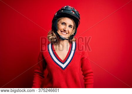 Middle age beautiful blonde motorcyclist woman wearing moto helmet over red background with a happy and cool smile on face. Lucky person.
