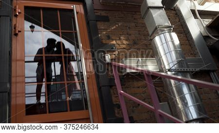 Glass Door With The Reflection Of Loving Man And Woman Kissing Lips. Action. Reflection Of A Beautif