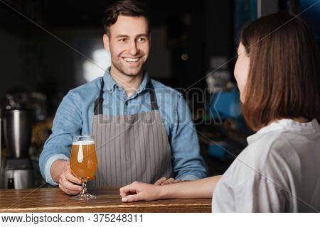 Beer For Regular Client. Smiling Bartender Gives To Girl Bright Lager Behind Bar In Interior Of Pub