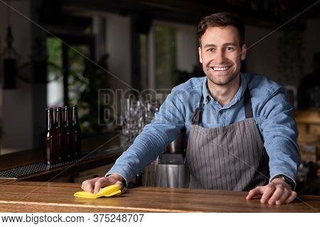 Meeting Client In Pub. Smiling Pretty Barman In Apron With Sponge Wipes Bar Counter In Interior
