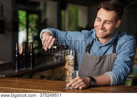 Cocktail From Bartender. Smiling Barman In Apron Pours Drink Into High Glass With Ice In Interior Of