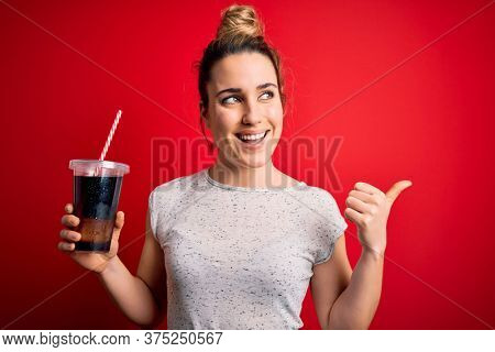 Beautiful blonde woman drinking cola fizzy beverage to refreshment over red background pointing and showing with thumb up to the side with happy face smiling