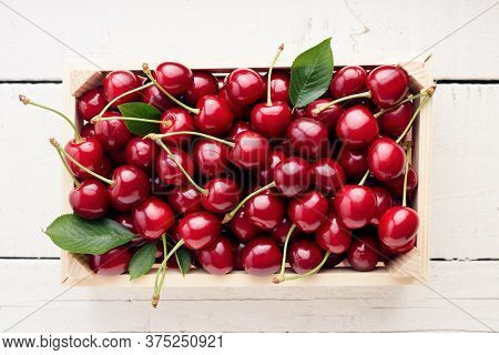 Fresh, ripe sweet cherries in small wooden crate on white table