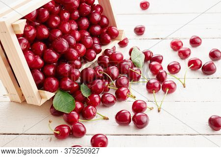Fresh, ripe sweet cherries spilling from a small wooden crate