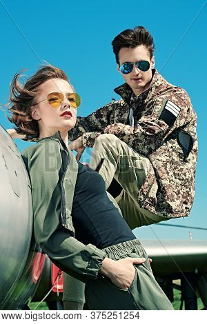 A beautiful girl and a handsome man pilots is posing next to a fighter jet at the airfield. Military aircraft. Military fashion.
