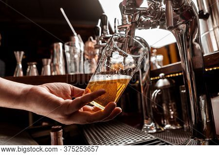 Pour A Pint Of Beer. Bartenders Hand Holds Glass And Takes Drink From Tap In Interior Of Pub