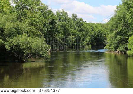 A River Forest View With Tree Lined Reflection And Blue Sky