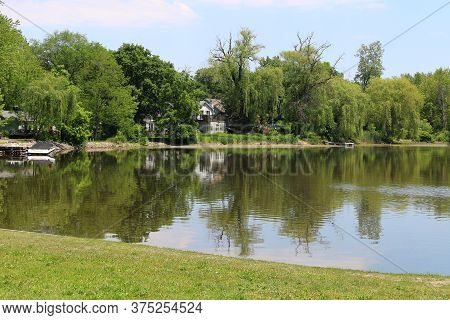 Bright Sunny Day With A Tree Lined Lake And Reflection With A Blue Sky