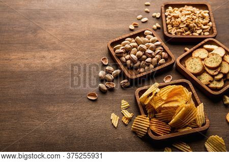 Crispy Snacks. Rusks, Peanuts Pistachios And Chips In Square Wooden Plates On Brown Table, Close Up,