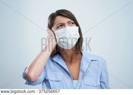 Attractive woman wearing protective mask isolated over white background