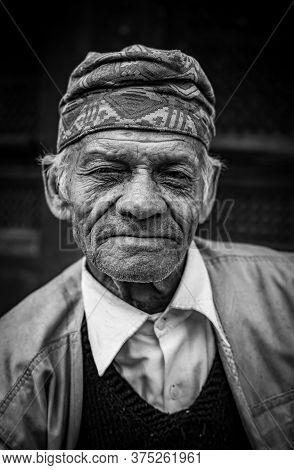 Black And White Portraiture Of A Middle-aged Asian Man Smiling At The Camera.