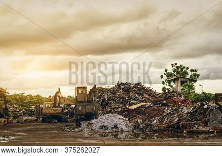Pile Of Garbage And Backhoe At Waste Depot. Rubbish Recycling Business. Heap  Of Plastic Waste, Wood