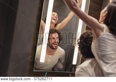 Beautiful Young Couple In Love Wearing Pajamas, Standing In Front Of Bathroom Mirror Next To A Sink,