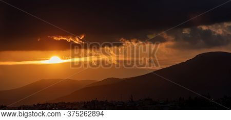 Sunset, Sunrise Through And Behind The Clouds Over Mountains Background.