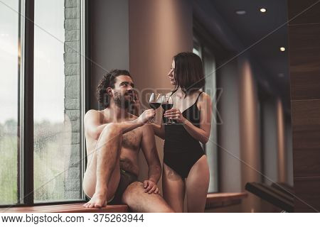 Couple In Love Enjoying Their Vacation, Relaxing At Spa Center, Sitting By The Window Near The Swimm