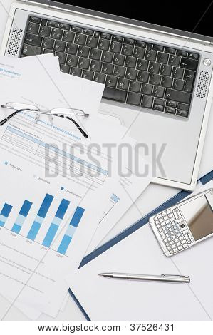 Business accessories stacked chart phone laptop lying office desk