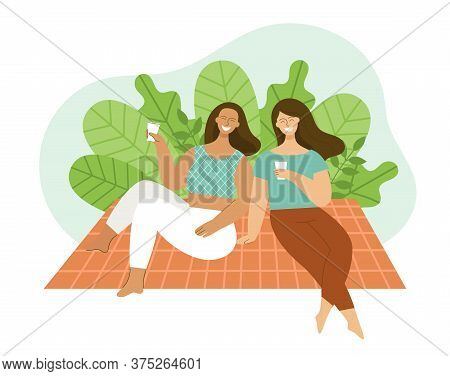 Two Young Women Are Sitting On A Plaid In A Park. Friends Are Laughing And Talking. Concept Of A Pic