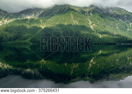 Mysterious Foggy Green Mountain Forrest And Hills With A Reflection On The Lake, Morskie Oko In High