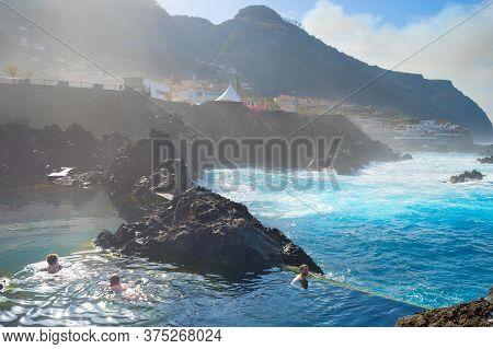 Porto Moniz, Madeira, Portugal - Feb 03, 2020: People Bathes In Natural Lava Ocean Pools. Lava Pools