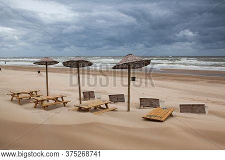 Egmont Aan Zee, Netherland - June 29,2020: The Empty Restaurant On The Beach. The Sand-covered Table