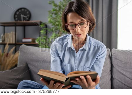 Chrming Woman In Eyeglasses And Blue Shirt Getting Interested While Reading New Book At Home. Concep