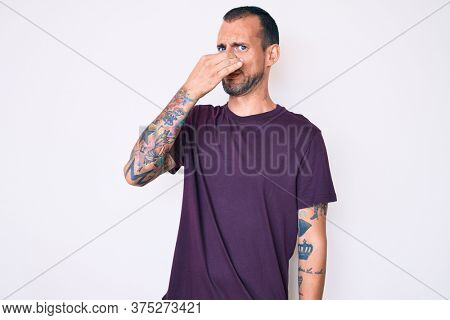 Young handsome man with tattoo wearing casual clothes smelling something stinky and disgusting, intolerable smell, holding breath with fingers on nose. bad smell