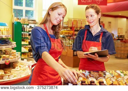 Trainee helps store manager in the supermarket with an inventory