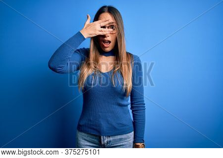 Young beautiful blonde woman with blue eyes wearing glasses standing over blue background peeking in shock covering face and eyes with hand, looking through fingers with embarrassed expression.
