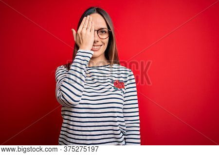 Young beautiful blonde woman with blue eyes wearing glasses standing over red background covering one eye with hand, confident smile on face and surprise emotion.