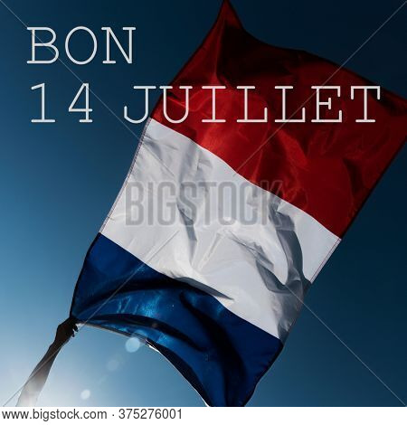 man holding a French flag waving on the wind and the text bon 14 juillet, happy 14 july, the national day of France written in French, against the blue sky, in backlit