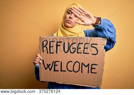 Beautiful arab woman wearing islamic hijab holding banner with refugees welcome message with open hand doing stop sign with serious and confident expression, defense gesture