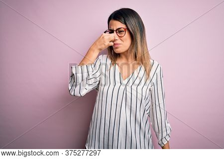 Young beautiful woman wearing casual striped t-shirt and glasses over pink background smelling something stinky and disgusting, intolerable smell, holding breath with fingers on nose. Bad smell