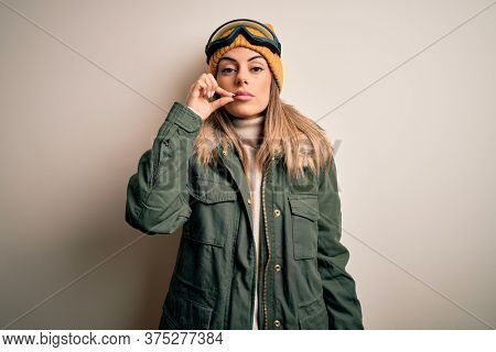 Young brunette skier woman wearing snow clothes and ski goggles over white background mouth and lips shut as zip with fingers. Secret and silent, taboo talking