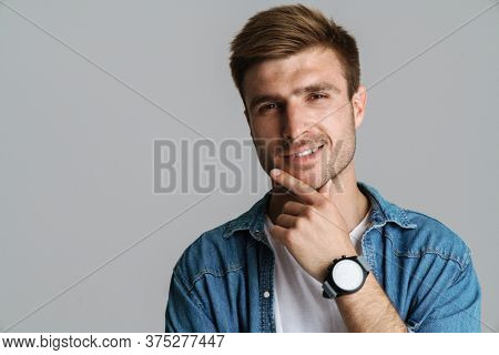 Portrait of brutal pleased man with wristwatch smiling and looking at camera isolated over grey background