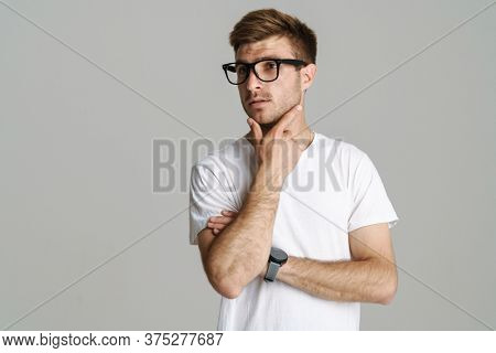 Portrait of redhead puzzled man in eyeglasses posing and thinking at camera isolated over grey background