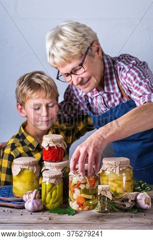 Happy Senior Mature Woman, Grandmother And Young Boy, Grandson Holding In Hands Jars With Homemade P